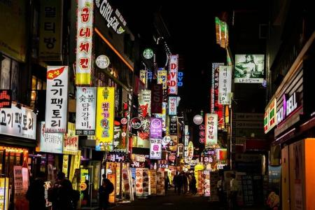 Street in Seoul at night with shop and restaurant signs alight
